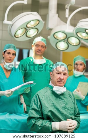 Surgeon sitting while crossing his hands with a team behind him in a surgical room - stock photo