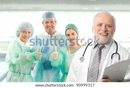 Surgeon team lead by senior white haired doctor looking at camera, smiling.? - stock photo