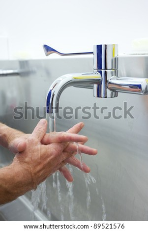 Surgeon washing hands prior to operation using correct technique for cleanliness