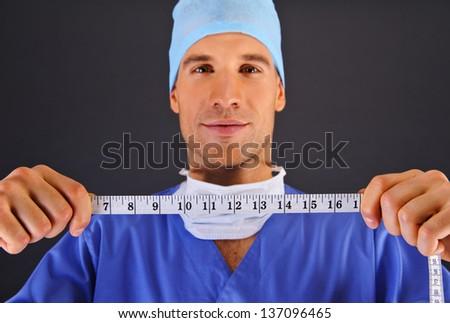Surgeon with centimeter over dark background - stock photo
