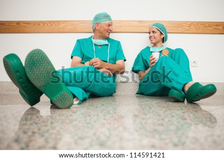 Surgeons talking while sitting in the floor in hospital - stock photo