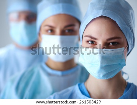 Surgeons team, man and woman wearing protective uniforms,caps and masks.  - stock photo