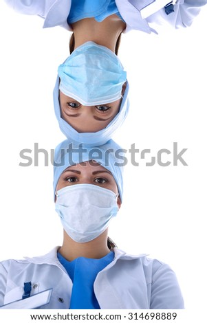 Surgeons team, man and woman wearing protective uniforms,caps and masks