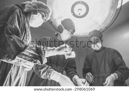 Surgeons team standing above of the patient before surgery with equipment , selective focus on hand , Black and white,noise and film grain style - stock photo
