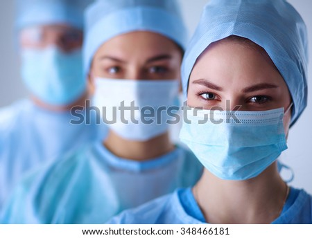 Surgeons team, wearing protective uniforms,caps and masks  - stock photo
