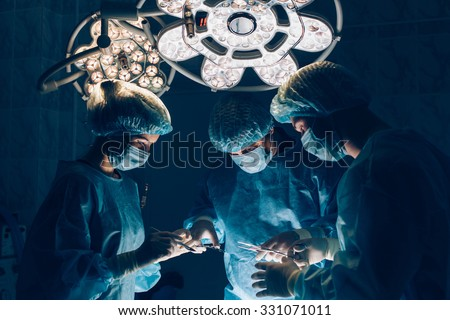 Surgeons team working with Monitoring of patient in surgical operating room. breast augmentation. - stock photo