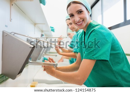 Surgeons washing their hands in a hospital while smiling