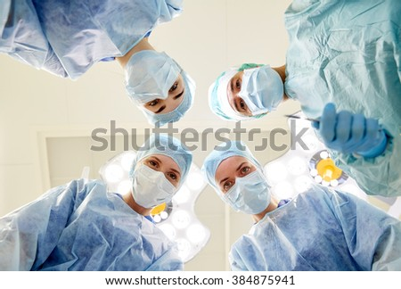 surgery, medicine and people concept - group of surgeons in operating room at hospital looking into camera