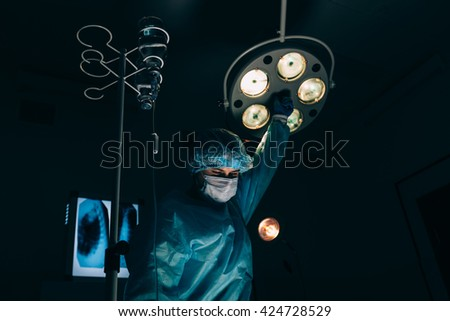 surgery, medicine and people concept - surgeon in mask adjusting lamp  operating room at hospital