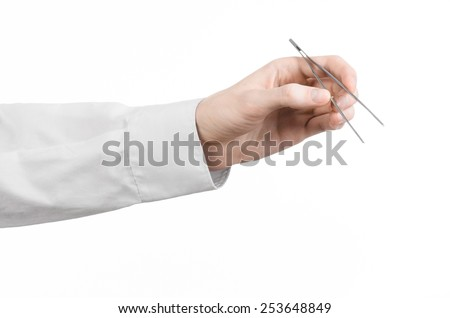 Surgical and Medical theme: a doctor's hand holding tweezers isolated on white background in studio - stock photo