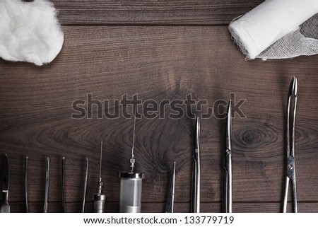 surgical armaments on the brown wooden background - stock photo