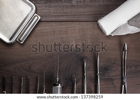 surgical armaments on the dark brown wooden background - stock photo