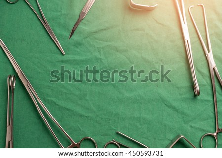surgical instruments and tools including scalpels, forceps and tweezers arranged on a table for a surgery - stock photo