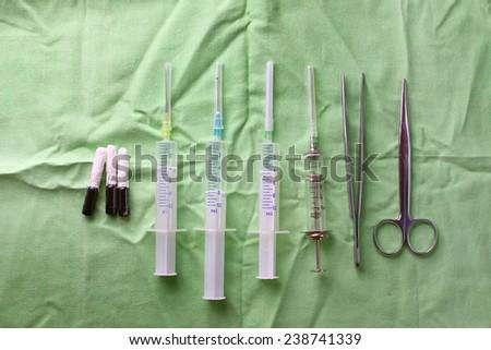 surgical syringe scissors tweezer and iodine ampules - stock photo
