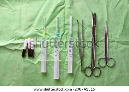 surgical syringe scissors tweezers and iodine ampules - stock photo