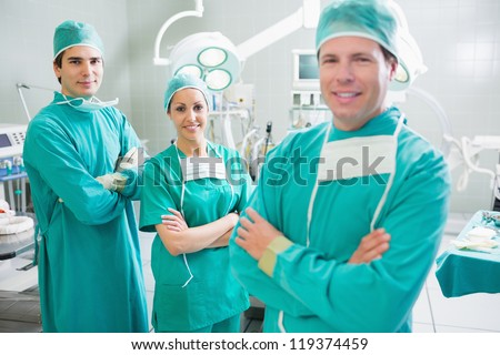 Surgical team with arms crossed smiling in an operating theatre - stock photo