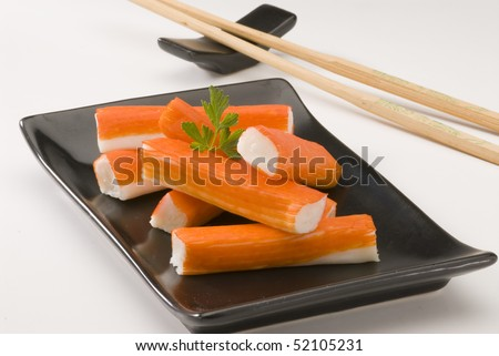 Surimi or crab sticks in a black ceramic plate. Selective focus. White background.
