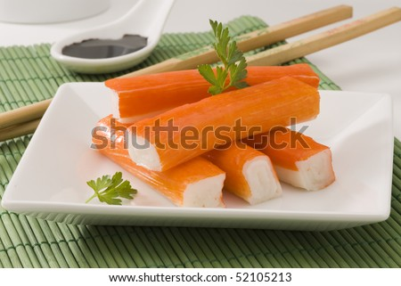 Surimi or crab sticks in a white plate. Selective focus. White background.