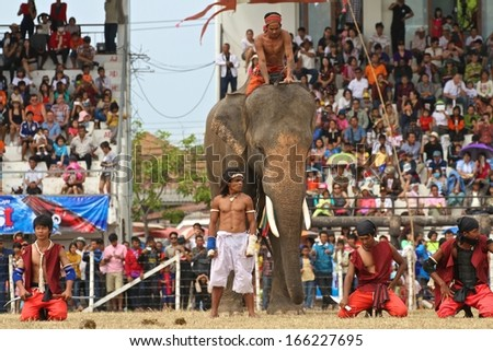 SURIN, THAILAND - NOVEMBER 17: An elephant and mahouts playing warriors taking part in a reenactment of a battle at the Elephant Roundup Festival held at Surin, Thailand on the 17th November, 2013.