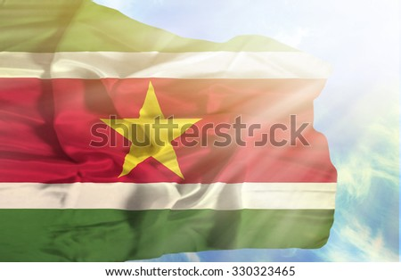 Suriname waving flag against blue sky with sunrays - stock photo