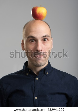surprides bald young man with an apple on his head - stock photo