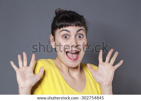 surprise and success concept - cute 20s brunette woman using both hands and facial expression for surprise and happiness - stock photo