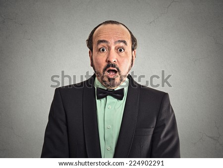 Surprise astonished man. Closeup portrait man looking surprised in full disbelief wide open mouth isolated grey background. Positive human emotion facial expression body language. Headshot funny guy - stock photo