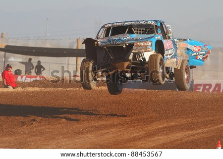 SURPRISE, AZ - APR 16: Robby Woods (99) flys over a jump in Pro 2 Unlimited Lucas Oil Off Road Series racing on April 16, 2011 at Speedworld Off Road Park in Surprise, AZ. - stock photo