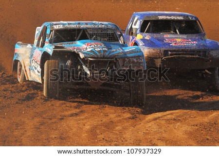 SURPRISE, AZ - APR 16: Robby Woods (99) leads Bryce Menzies (7) during Pro 2 Unlimited Lucas Oil Off Road Series racing on April 16, 2011 at Speedworld Off Road Park in Surprise, AZ. - stock photo