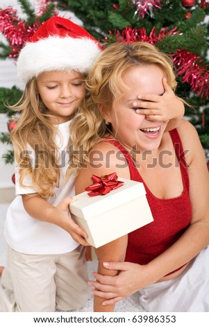 Surprise christmas present - little girl and woman in front of the decorated tree - stock photo