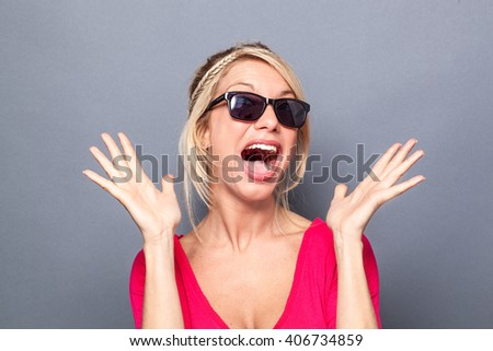 surprise concept - bubbly young blond woman looking like a star with her sunglasses, using both hands and facial expression for surprise and happiness, grey background studio - stock photo