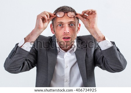 surprise concept - stunned 40s entrepreneur holding his eyeglasses on the forehead, finding a great idea or perspective to his business, grey background studio