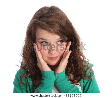 Surprise expression of beautiful young teenager girl with big blue eyes wide open and hands raised to her face. Girl has long brown hair and wearing green hoodie jumper.