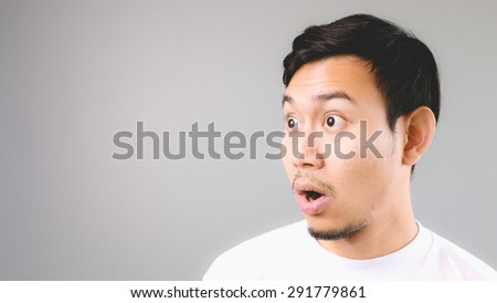 Surprise face on empty copyspace. An asian man with white t-shirt and grey background. - stock photo