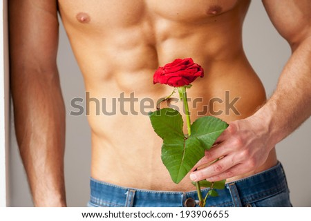 Surprise for her. Close-up of young muscular man with perfect torso holding red rose while leaning at the wall