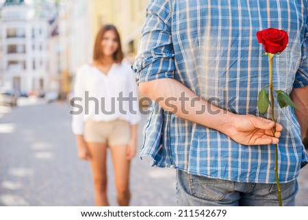 Surprise for her. Rear view of young man holding red rose behind his back while woman walking in the background  - stock photo