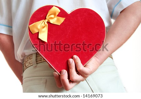 Surprise gift, Man with Luxury Heart Shaped velvet Box of Chocolates behinf back - stock photo
