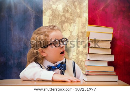 Surprise pupil looking at books against france flag in grunge effect - stock photo