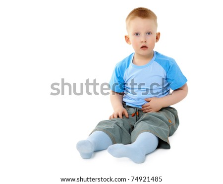 Surprised a little boy sitting isolated on white background - stock photo
