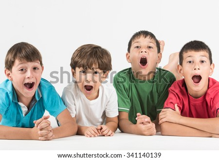 Surprised and excited  4 boys looking at camera while lying on floor - stock photo