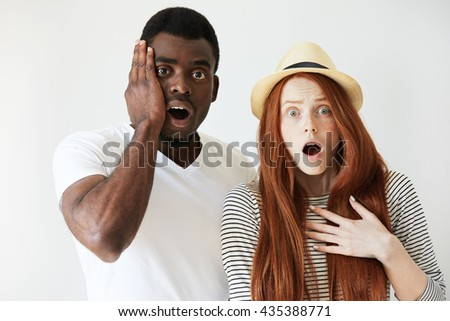 Surprised and horrified couple looking at camera with eyes wide-opened. Afro American man slapping face with hand in terror, Caucasian girl in summer hat looks shocked and worried by bad news.