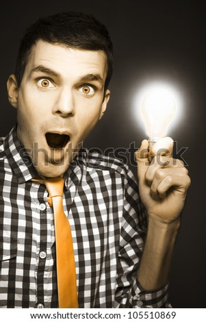 Surprised And Shocked Business Man Holding Illuminated Light Bulb In Hand While Depicting A Creative Solution Of Business Success - stock photo