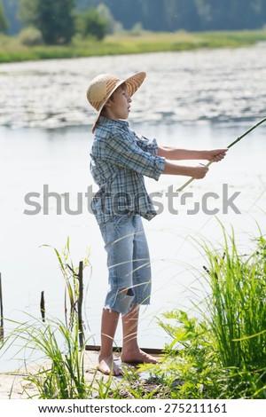 Surprised angler boy is throwing bait of handmade fishing rod full length shot - stock photo