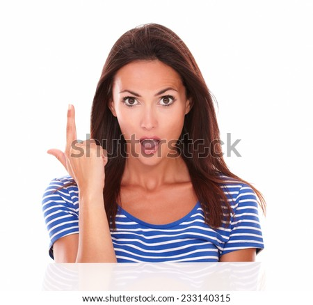 Surprised attractive lady pointing up as holding a gun while looking at camera, front view in white background - copyspace