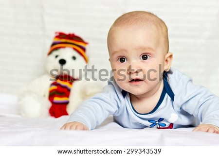 Surprised baby boy portrait lying on bed with plush teddy bear - stock photo