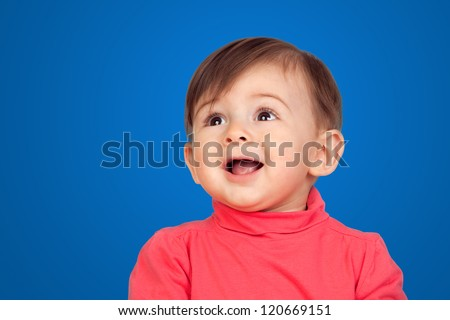 Surprised baby girl looking up isolated on blue background - stock photo
