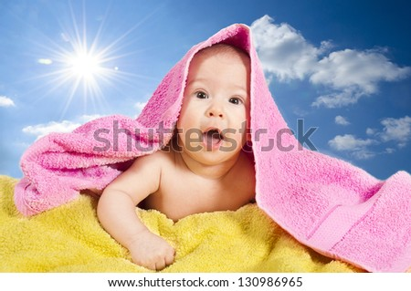 Surprised baby girl with towels over her head - stock photo