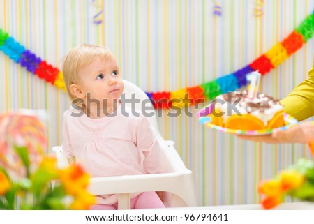 Surprised baby unexpecting birthday cake surprise