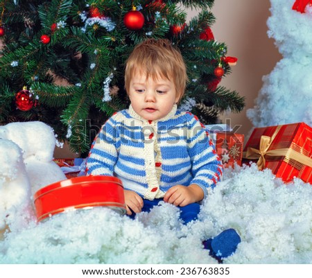 Surprised baby with Christmas presents near decorated fir tree - stock photo