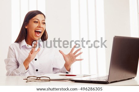Surprised beautiful business woman working at a laptop in office